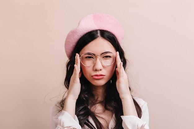 カメラを見て眼鏡をかけて物思いにふける中国人女性。ベージュの背景にポーズをとるベレー帽の面白いアジアのモデル。
