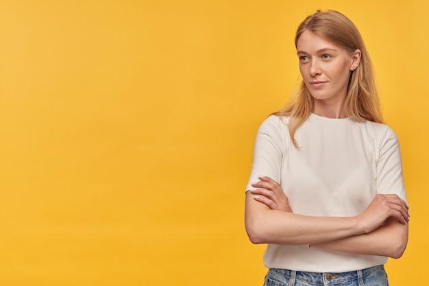 腕を組んで立って、黄色のコピースペースで横を向いて立っている白いtシャツのそばかすのある物思いにふける自信のある女性