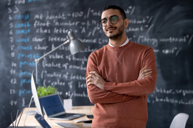 Pensive confident young middle-eastern programmer with beard standing with crossed arms in office with computer language code on blackboard
