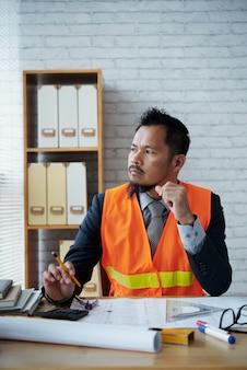 青写真でオフィスの机に座っている物思いにふける建設エンジニア