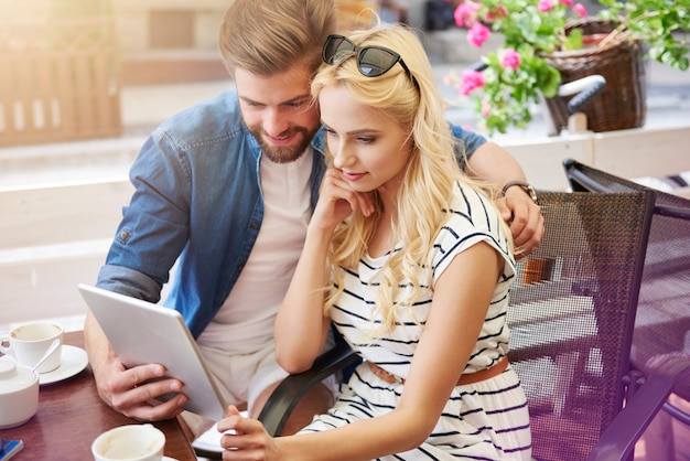 Задумчивая пара с помощью цифрового планшета в кафе