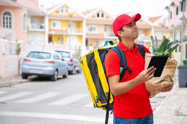 태블릿을 사용하여 주소를 확인하는 등온 음식 배낭이있는 잠겨있는 택배. 중간 샷, 복사 공간. 통신 또는 배달 서비스 개념