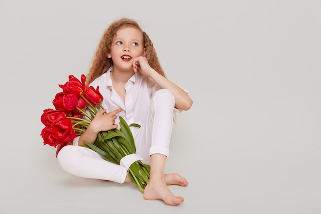 Задумчивая любопытная девочка в белом элегантном наряде обнимает красные тюльпаны, смотрит в сторону, сидит на полу, держа руку на щеке