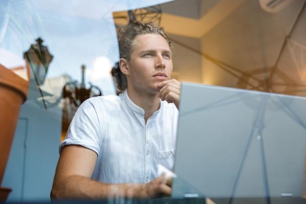Задумчивый кудрявый деловой человек смотрит в сторону, сидя за столом с портативным компьютером в кафе