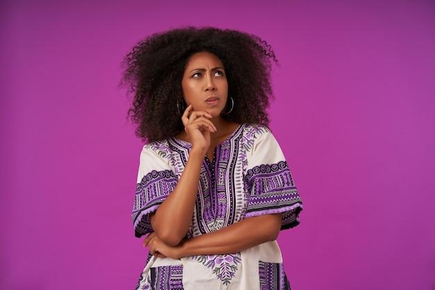 Donna dalla pelle scura riccia pensierosa in abiti casual isolati su viola, tenendo il mento con la mano alzata e guardando pensieroso verso l'alto, aggrottando le sopracciglia con le labbra piegate