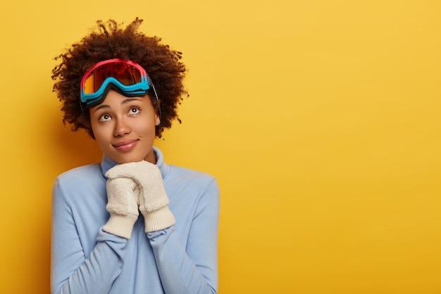 La sciatrice riccia pensierosa indossa un maglione blu caldo e guanti bianchi, ha la maschera da snowboard sulla testa, si erge su sfondo giallo.