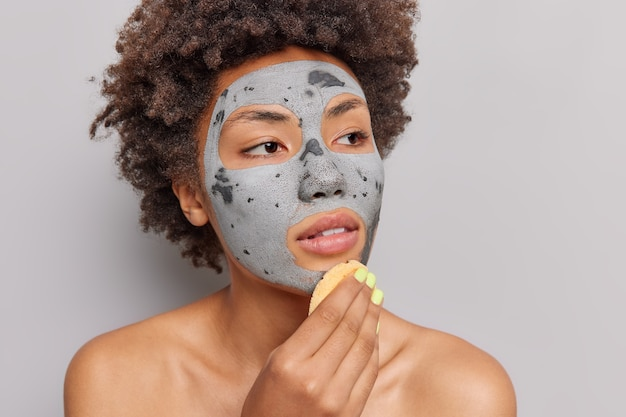 Pensive curly haired african american woman focused into distance applies clay mask