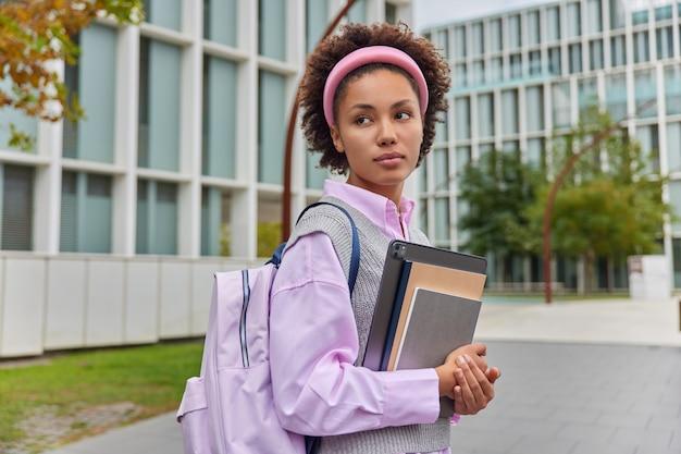 物思いにふける縮れ毛の学生はメモ帳を持ち、都会の環境でデジタルタブレットを散歩し、カジュアルな服を着て屋外で休憩し、モダンなガラスの建物にバックパックスタンドを持ちます