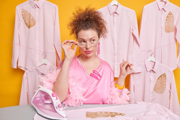Pensive curly haired woman keeps hand on rim of spectacles dressed in silk gown poses near ironing board with electric iron poses against shirts on hangers thinks how to finish domestic work in time