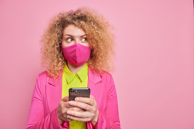 Pensive curly haired woman looks away types text messages dressed in formal clothes protects herself with coronavirus mask poses against pink wall with blank copy space for your promo.