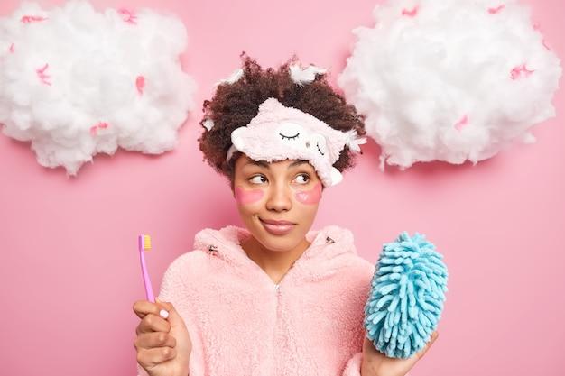 머리에 깃털을 가진 잠겨있는 곱슬 머리 여자는 깨어 난 후 미용 및 위생 절차를 거치며 칫솔 샤워 스폰지가 신중하게 분홍색 벽 위에 고립 된 것처럼 보입니다.