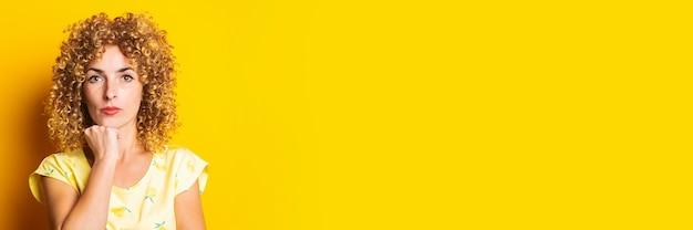 黄色の背景に彼女のあごの下に拳を保持している物思いにふける縮れ毛の若い女性