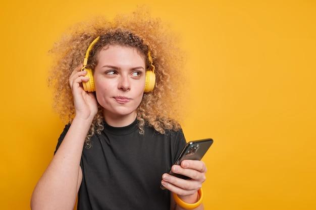잠겨있는 곱슬 머리 젊은 여자는 귀에 스테레오 헤드폰을 착용 좋아하는 음악을 듣고 휴대 전화 응용 프로그램을 사용하여 빈 공간이 노란색 벽에 캐주얼 블랙 티셔츠 포즈를 착용