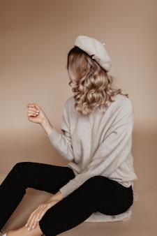 彼女の爪を見ている物思いにふける巻き毛の女性
