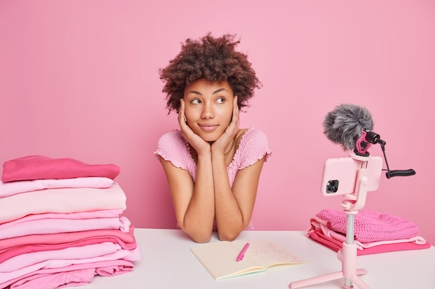 Pensive curly woman looks away with thoughtful expression thinks about new content for blog poses in front of smartphone camera on tripod surrounded by piles of folded laundry does domestic chores