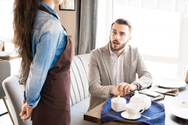 Pensive customer asking waitress in cafe