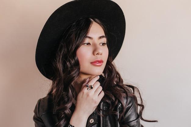 物思いにふけるかわいいアジアの女性が目をそらします。帽子をかぶった巻き毛の魅力的な中国人女性のスタジオショット。