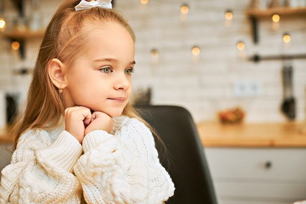Pensive cute european little girl in knitted jumper holding both hands at her face and looking away, thinking about something, waiting mother from work. adorable baby child sitting in kitchen alone