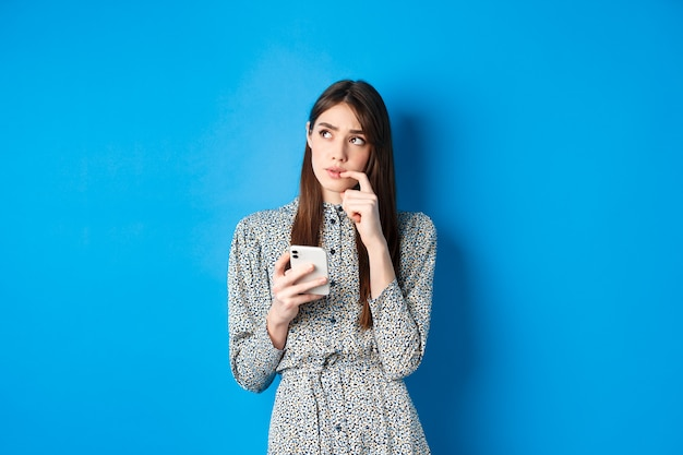 メッセージに答える方法を考え、思慮深く脇を見て、スマートフォンを持って、青いドレスを着て立っている物思いにふけるかわいい女の子。