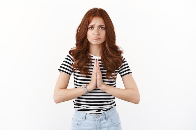 수심에 찬 빨간 머리 소녀는 후회하며 구걸하고, 삐죽삐죽하고, 눈썹을 찡그리며, 손을 잡고, 기도하고 사과하고, 순진한 연민의 표정으로 괴로워하며 서 있습니다.