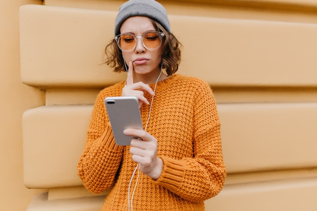 Pensive cute woman in oversize sweater looking at phone screen walking down the street