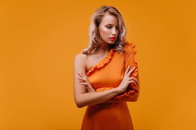 Задумчивая милая женщина с вьющимися волосами, стоящая со скрещенными руками на желтой стене