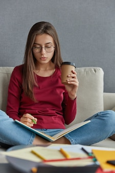 잠겨있는 검은 머리의 여성 그래픽 디자이너는 노트북에 표기하고, 정보를 기록하고, 다리를 꼬고, 일회용 커피 한잔을 나른다.