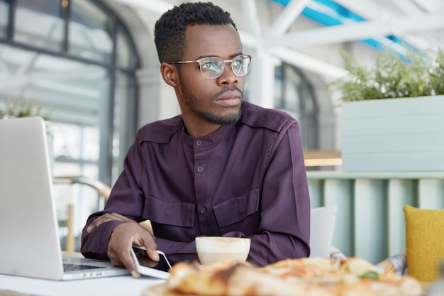 Pensive dark skinned african male freelancer in elegant shirt, works on new project, holds modern smart phone, drinks coffee