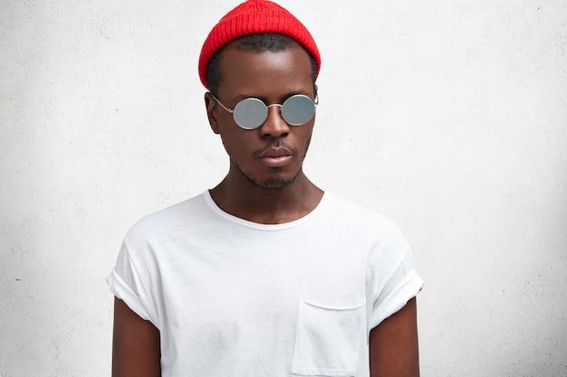 잠겨있는 어두운 피부의 세련된 힙 스터 남자가 캐주얼 한 빨간 모자와 트렌디 한 선글라스를 착용하고 여가 시간에 재현