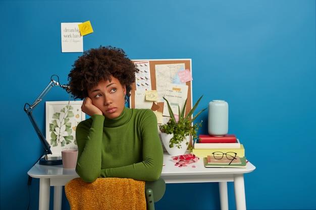 緑のタートルネックに身を包んだ物思いにふける暗い肌の女性は目をそらし、デスクトップで働いた後休憩し、青い背景に対して自宅でポーズをとります。