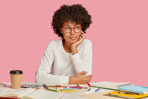Pensive dark skinned student studies art alone, likes drawings, wears spectacles, looks aside with thoughtful expression, has crisp hair, uses notepad with blank sheets, isolated on pink wall