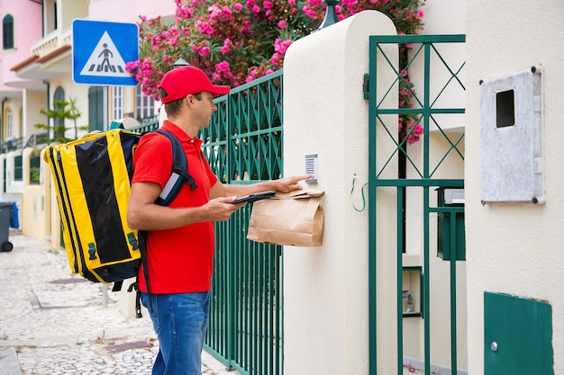 受信者のドアベルで鳴っている赤い帽子の物思いにふける配達員。黄色のサーマルバックパックを備えた中年の宅配便で、急行注文を行い、路上に立っています。配送サービスとポストコンセプト