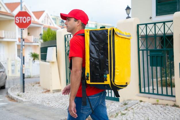 必要な家を見て赤い帽子をかぶった物思いにふける配達員。黄色のサーマルバックパックを備えた中年の宅配便で、急行注文を出し、通りを歩きます。配送サービスとオンラインショッピングのコンセプト