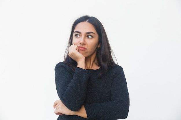 Pensive disappointed woman leaning chin on hand