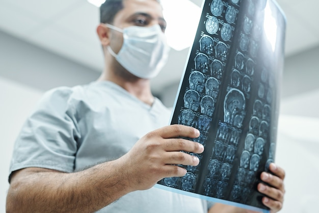 Задумчивый врач и медсестра в хирургических масках анализируют рентгеновское изображение, пока пациент спит в больничной палате