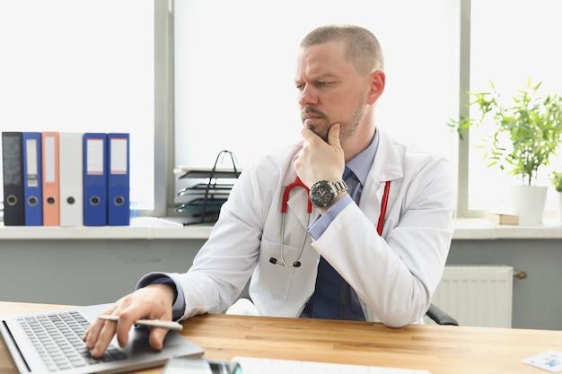 ノートパソコンの画面を見て、クリニックでキーボードで入力する物思いにふける医師。オンライン医療トレーニングの概念