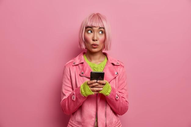 밥 헤어 스타일을 가진 잠겨있는 의심스러운 여자, 소셜 네트워크를 통해 뉴스 피드를 탐색하고 집중된 표현으로 신중하게 외모
