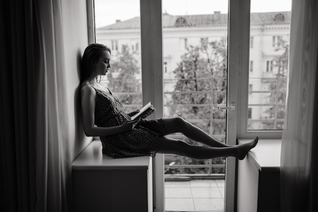 Pensive dreamy female holding book at home looking at big window dreaming, thoughtful young woman, student