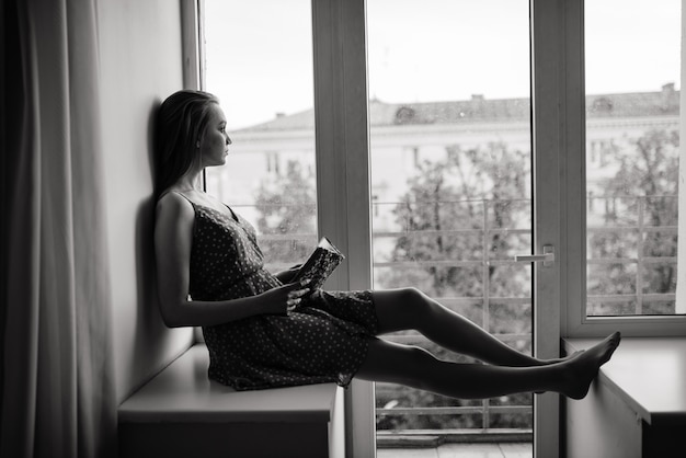 Pensive dreamy female holding book at home looking at big window dreaming