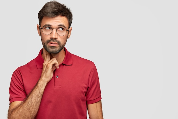 Pensive dreamy male with european appearance looks thoughtfully upwards, thinks about something, analyzes life situation, wears red t-shirt, stands against white wall with free blank space
