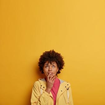 아프로 머리카락이 위에 집중된 잠겨있는 꿈꾸는 여성, 결정을 내리고, 신중하게 쳐다보고, 손을 입 근처에 유지하고, 노란색 아노락을 입습니다.