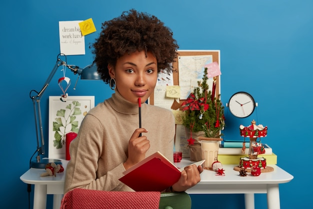 Задумчивая мечтательная молодая женщина записывает заметки, создает сочинение на интересную тему, держит карандаш и раскрывает красный блокнот