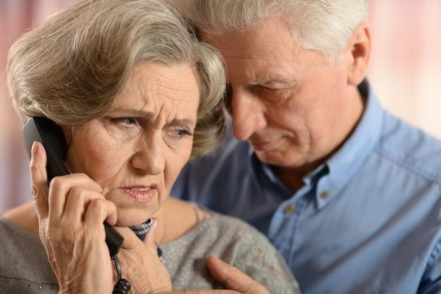 Задумчивая пожилая женщина и мужчина звонят по телефону