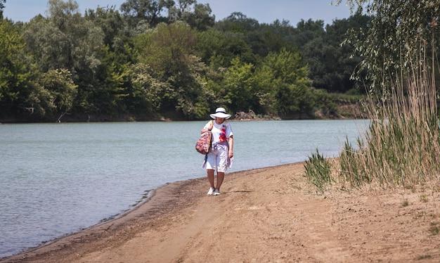 잠겨있는 노인 여성, 노인 연금 수급자, 강가의 모래 위에서 휴식, 시간과 나이의 개념, 신선한 공기 속에서의 여름 휴가, 건강한 라이프 스타일