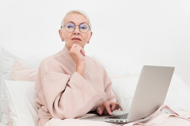 Pensive elderly woman posing in bed with laptop