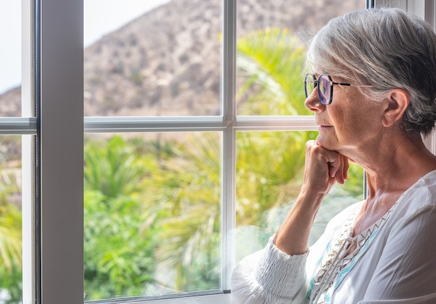 Pensive elderly woman at the window looking out