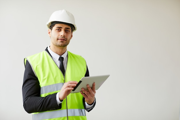 Pensive engineer holding tablet