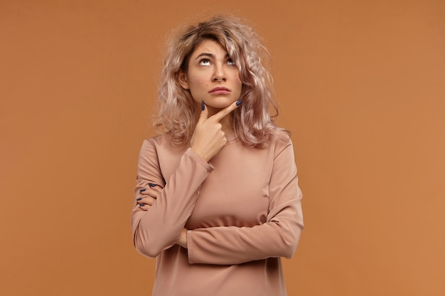 Donna europea pensierosa sulla ventina che fa programmi per il fine settimana, si massaggia il mento e guarda in alto
