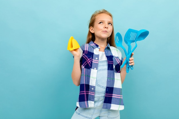 Pensive european girl holding a oven mitts and cutlery in hands on light blue