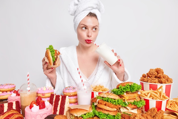 Pensive european lady with red painted lips drinks soda eats burger looks away addicted to fast food